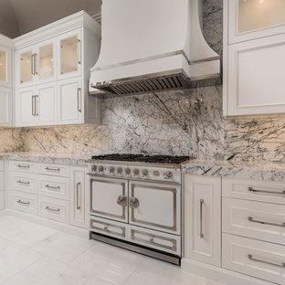 フェニックスの巨大な地中海スタイルのおしゃれなキッチン (エプロンフロントシンク、落し込みパネル扉のキャビネット、白いキャビネット、大理石カウンター、マルチカラーのキッチンパネル、大理石のキッチンパネル、シルバーの調理設備、大理石の床、マルチカラーの床、マルチカラーのキッチンカウンター) の写真