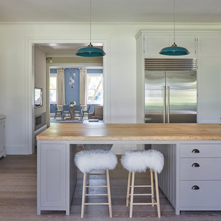 Large classic kitchen in London with a submerged sink, shaker cabinets, grey cabinets, an island, wood worktops, stainless steel appliances and light hardwood flooring.