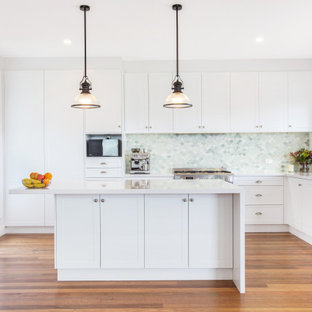 Inspiration for a mid-sized beach style u-shaped open plan kitchen in Central Coast with multi-coloured splashback, glass tile splashback, stainless steel appliances and with island.