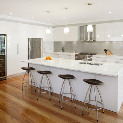 Inspiration for a mid-sized contemporary l-shaped medium tone wood floor kitchen remodel in Sydney with stainless steel appliances, an undermount sink, white cabinets, marble countertops, metallic backsplash, glass sheet backsplash and an island