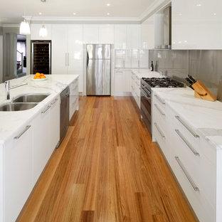 Mid-sized modern kitchen inspiration - Kitchen - mid-sized modern l-shaped light wood floor kitchen idea in Sydney with an undermount sink, white cabinets, marble countertops, metallic backsplash, glass sheet backsplash, stainless steel appliances and an island