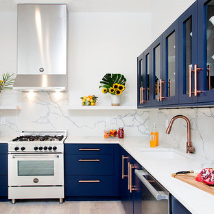 Inspiration for a contemporary l-shaped kitchen in New York with an undermount sink, flat-panel cabinets, blue cabinets, white splashback, stainless steel appliances, light hardwood floors, no island and beige floor.