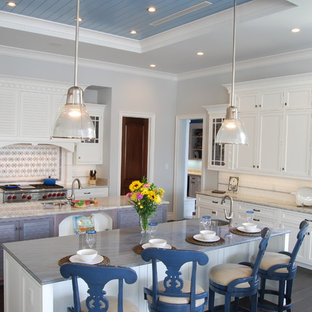 Photo of a large beach style open plan kitchen in Cincinnati with a double-bowl sink, recessed-panel cabinets, white cabinets, granite benchtops, white splashback, ceramic splashback, stainless steel appliances, ceramic floors and multiple islands.