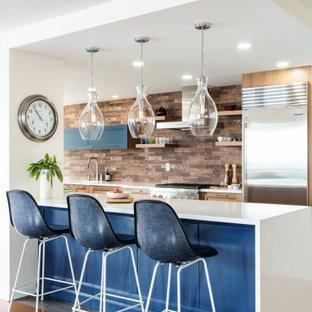 ニューアークのトランジショナルスタイルのおしゃれなキッチン (アンダーカウンターシンク、落し込みパネル扉のキャビネット、中間色木目調キャビネット、赤いキッチンパネル、シルバーの調理設備の、無垢フローリング、茶色い床、白いキッチンカウンター) の写真