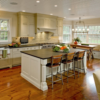Eat-in kitchen - large traditional l-shaped medium tone wood floor eat-in kitchen idea in Philadelphia with a farmhouse sink, recessed-panel cabinets, beige cabinets, soapstone countertops, multicolored backsplash, mosaic tile backsplash, stainless steel appliances and an island