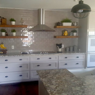 Large country kitchen in Dallas with a farmhouse sink, shaker cabinets, beige cabinets, granite benchtops, beige splashback, subway tile splashback, white appliances, dark hardwood floors, with island, brown floor and multi-coloured benchtop.
