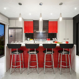Photo of a small modern galley eat-in kitchen in Sydney with a double-bowl sink, flat-panel cabinets, red cabinets, quartz benchtops, black splashback, mosaic tile splashback, stainless steel appliances, ceramic floors and with island.