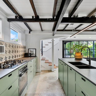 Design ideas for a large transitional galley open plan kitchen in Brisbane with a double-bowl sink, flat-panel cabinets, green cabinets, quartz benchtops, ceramic splashback, concrete floors, with island, multi-coloured splashback, black appliances, beige floor, black benchtop and exposed beam.