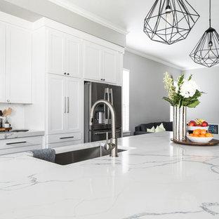 Inredning av ett klassiskt stort vit vitt kök med öppen planlösning, med en undermonterad diskho, skåp i shakerstil, vita skåp, bänkskiva i kvartsit, vitt stänkskydd, stänkskydd i keramik, rostfria vitvaror, mörkt trägolv, en köksö och brunt golv
