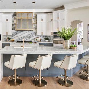 オースティンの中くらいのトランジショナルスタイルのおしゃれなキッチン (シェーカースタイル扉のキャビネット、マルチカラーのキッチンパネル、シルバーの調理設備、淡色無垢フローリング、エプロンフロントシンク、グレーのキャビネット、珪岩カウンター、大理石のキッチンパネル、グレーの床、青いキッチンカウンター) の写真