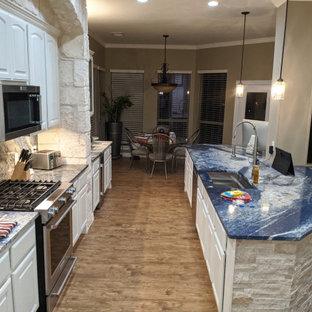 Пример оригинального дизайна: огромная кухня в современном стиле с обеденным столом, врезной раковиной, фасадами с выступающей филенкой, белыми фасадами, гранитной столешницей, синим фартуком, фартуком из гранита, техникой из нержавеющей стали, полом из ламината, островом, коричневым полом и синей столешницей