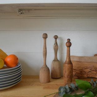 ポートランドの小さいラスティックスタイルのおしゃれなキッチン (エプロンフロントシンク、シェーカースタイル扉のキャビネット、緑のキャビネット、木材カウンター、白いキッチンパネル、木材のキッチンパネル、シルバーの調理設備、リノリウムの床) の写真