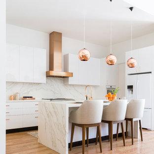 Modern inredning av ett vit vitt l-kök, med släta luckor, vita skåp, vitt stänkskydd, stänkskydd i sten, vita vitvaror, mellanmörkt trägolv, en köksö och brunt golv