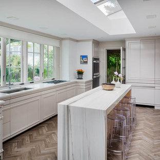 Esempio di una grande cucina ad U design chiusa con lavello sottopiano, ante lisce, ante bianche, top in quarzo composito, paraspruzzi bianco, elettrodomestici bianchi, pavimento in legno massello medio e isola