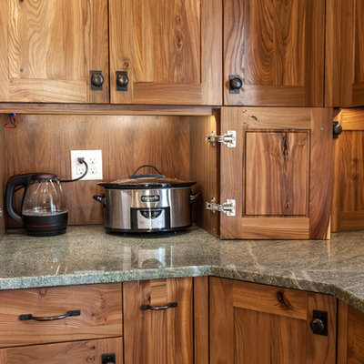 Inspiration for a mid-sized craftsman l-shaped porcelain tile eat-in kitchen remodel in Denver with a farmhouse sink, recessed-panel cabinets, medium tone wood cabinets, granite countertops, green backsplash, glass tile backsplash, paneled appliances and an island
