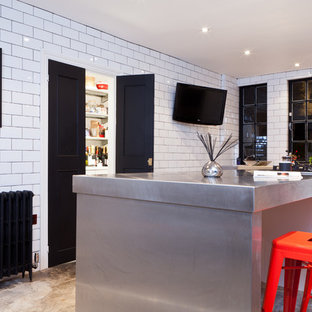 Example of a minimalist kitchen design in Birmingham with stainless steel countertops, white backsplash, subway tile backsplash, recessed-panel cabinets and black cabinets