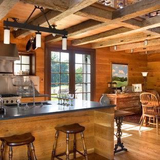 Design ideas for a mid-sized country eat-in kitchen in New York with open cabinets, medium wood cabinets, with island, an undermount sink, metallic splashback, stainless steel appliances, medium hardwood floors and soapstone benchtops.