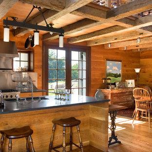 Свежая идея для дизайна: кухня среднего размера в стиле кантри с обеденным столом, открытыми фасадами, фасадами цвета дерева среднего тона, островом, врезной раковиной, фартуком цвета металлик, техникой из нержавеющей стали, паркетным полом среднего тона и столешницей из талькохлорита - отличное фото интерьера