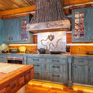 Inspiration for a large country u-shaped separate kitchen in Wichita with louvered cabinets, distressed cabinets, zinc benchtops, brown splashback, timber splashback, panelled appliances, medium hardwood floors and with island.