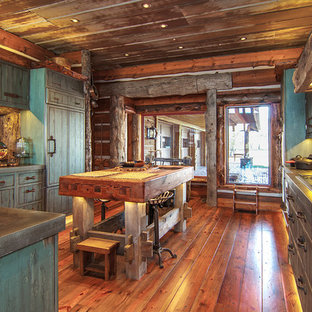 This is an example of a large country u-shaped separate kitchen in Wichita with louvered cabinets, distressed cabinets, zinc benchtops, brown splashback, timber splashback, panelled appliances, medium hardwood floors and with island.