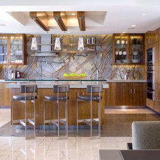 マイアミの大きいコンテンポラリースタイルのおしゃれなキッチン (ガラス扉のキャビネット、中間色木目調キャビネット、茶色いキッチンパネル、石スラブのキッチンパネル、シルバーの調理設備の、珪岩カウンター、ライムストーンの床、白い床) の写真