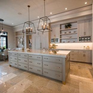 Inredning av ett klassiskt stort grå grått kök, med släta luckor, grå skåp, bänkskiva i kvarts, integrerade vitvaror, marmorgolv, en köksö och brunt golv