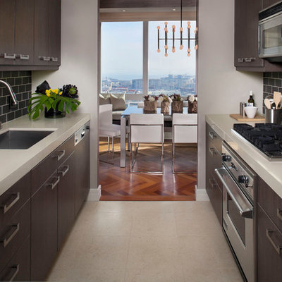 Enclosed kitchen - contemporary galley enclosed kitchen idea in San Francisco with subway tile backsplash, stainless steel appliances, an undermount sink, flat-panel cabinets and dark wood cabinets