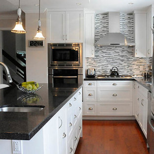 Design ideas for a mid-sized contemporary u-shaped eat-in kitchen in Vancouver with an undermount sink, shaker cabinets, grey splashback, stainless steel appliances, medium hardwood floors, with island, white cabinets, terrazzo benchtops and brown floor.