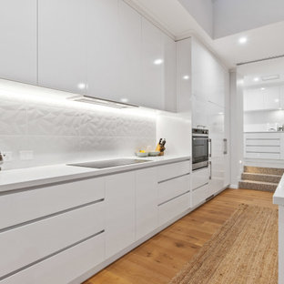 This is an example of a large contemporary l-shaped kitchen in Perth with an undermount sink, flat-panel cabinets, white cabinets, white splashback, panelled appliances, medium hardwood floors, with island, beige floor and white benchtop.