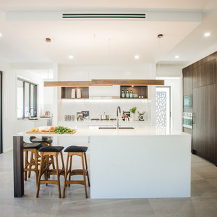 This is an example of a large contemporary galley open plan kitchen in Sydney with dark wood cabinets, quartz benchtops, white splashback, glass sheet splashback, stainless steel appliances, ceramic floors, with island, an undermount sink and grey floor.