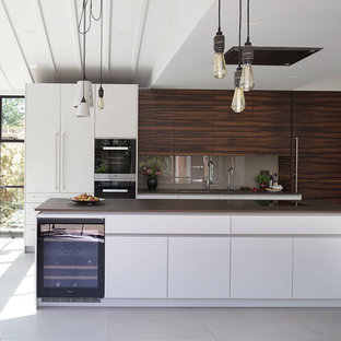 Design ideas for a large contemporary single-wall kitchen/diner in London with a submerged sink, engineered stone countertops, beige splashback, glass sheet splashback, an island, grey floors and brown worktops.
