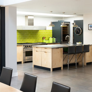 Design ideas for a contemporary galley kitchen/diner in Surrey with flat-panel cabinets, light wood cabinets, green splashback, metro tiled splashback, stainless steel appliances, a breakfast bar, grey floors and grey worktops.