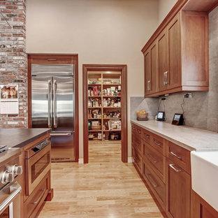 ロサンゼルスの中くらいのインダストリアルスタイルのおしゃれなキッチン (エプロンフロントシンク、シェーカースタイル扉のキャビネット、中間色木目調キャビネット、クオーツストーンカウンター、グレーのキッチンパネル、石スラブのキッチンパネル、シルバーの調理設備、淡色無垢フローリング、茶色い床) の写真