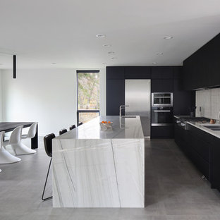 Modern eat-in kitchen pictures - Example of a minimalist l-shaped gray floor eat-in kitchen design in Milwaukee with a double-bowl sink, flat-panel cabinets, black cabinets, white backsplash, stainless steel appliances, an island and white countertops