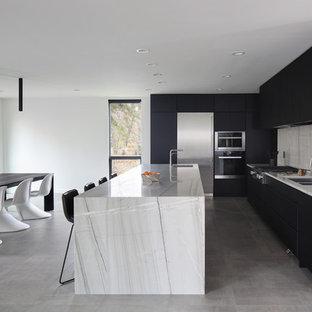 Foto de cocina comedor en L, minimalista, con fregadero de doble seno, armarios con paneles lisos, puertas de armario negras, salpicadero blanco, electrodomésticos de acero inoxidable, una isla, suelo gris y encimeras blancas