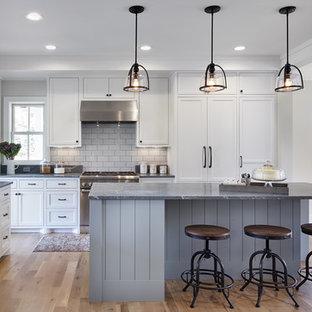 Mittelgroße Landhaus Wohnküche in L-Form mit Landhausspüle, weißen Schränken, Speckstein-Arbeitsplatte, Küchenrückwand in Weiß, hellem Holzboden, Kücheninsel, Kassettenfronten, Rückwand aus Steinfliesen, Elektrogeräten mit Frontblende und braunem Boden in Minneapolis