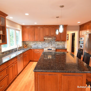 This is an example of a medium sized traditional u-shaped kitchen/diner in DC Metro with a double-bowl sink, raised-panel cabinets, medium wood cabinets, granite worktops, blue splashback, glass tiled splashback, stainless steel appliances, light hardwood flooring and an island.