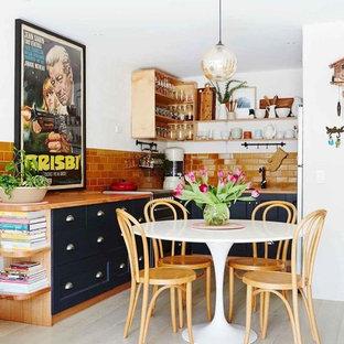 Imagen de cocina comedor en L, tradicional renovada, sin isla, con armarios con paneles empotrados, puertas de armario azules, encimera de madera, salpicadero naranja, salpicadero de azulejos tipo metro, suelo de madera pintada y suelo blanco