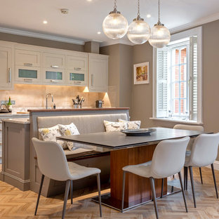 Inspiration for a transitional galley eat-in kitchen in Dublin with a drop-in sink, solid surface benchtops, beige splashback, black appliances, vinyl floors, with island, beige cabinets, grey benchtop, shaker cabinets and beige floor.
