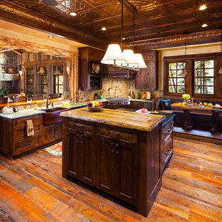 Example of a mountain style eat-in kitchen design in Denver with dark wood cabinets and beige backsplash
