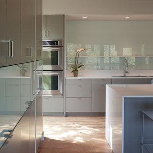 Пример оригинального дизайна: параллельная кухня среднего размера в стиле модернизм с техникой из нержавеющей стали, плоскими фасадами, серыми фасадами, столешницей из кварцевого агломерата, фартуком из стекла, обеденным столом, врезной раковиной, паркетным полом среднего тона, островом и коричневым полом
