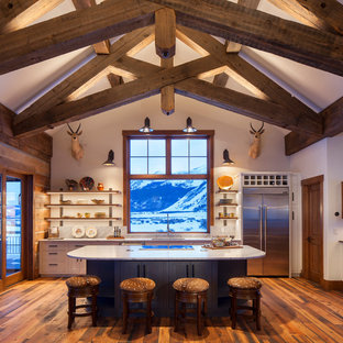 Photo of a rustic galley open plan kitchen in Denver with a submerged sink, shaker cabinets, white cabinets, stainless steel appliances, dark hardwood flooring, an island, brown floors and white worktops.