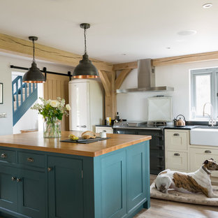 Inspiration for a country enclosed kitchen in West Midlands with a belfast sink, shaker cabinets, beige cabinets, black appliances, light hardwood flooring, an island and black worktops.