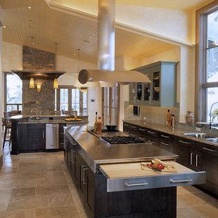Moderne Wohnküche in L-Form mit Doppelwaschbecken, Schrankfronten im Shaker-Stil, dunklen Holzschränken, Edelstahl-Arbeitsplatte, Küchenrückwand in Grau, Küchengeräten aus Edelstahl, Travertin und Kücheninsel in Denver