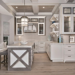 Inspiration for a beach style l-shaped kitchen in Miami with with island, a farmhouse sink, glass-front cabinets, beige cabinets, beige splashback, light hardwood floors and beige floor.