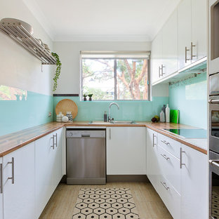 Small contemporary u-shaped separate kitchen in Sydney with white cabinets, wood benchtops, blue splashback, glass sheet splashback, stainless steel appliances, laminate floors, beige floor and flat-panel cabinets.