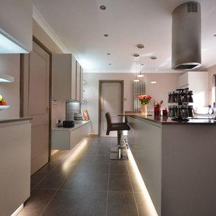 他の地域の中くらいのコンテンポラリースタイルのおしゃれなキッチン (ダブルシンク、フラットパネル扉のキャビネット、白いキャビネット、ラミネートカウンター、白いキッチンパネル、レンガのキッチンパネル、カラー調理設備、大理石の床、黒い床) の写真