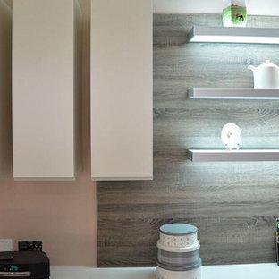 他の地域の中サイズのコンテンポラリースタイルのおしゃれなキッチン (ダブルシンク、フラットパネル扉のキャビネット、白いキャビネット、ラミネートカウンター、白いキッチンパネル、レンガのキッチンパネル、カラー調理設備、大理石の床、黒い床) の写真