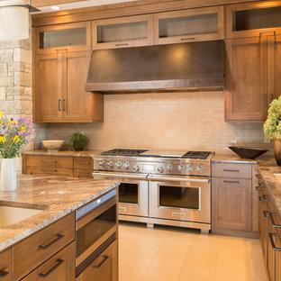 セントルイスの広いおしゃれなキッチン (アンダーカウンターシンク、落し込みパネル扉のキャビネット、中間色木目調キャビネット、クオーツストーンカウンター、茶色いキッチンパネル、磁器タイルのキッチンパネル、パネルと同色の調理設備、磁器タイルの床) の写真