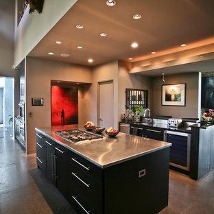 ボルチモアの大きいコンテンポラリースタイルのおしゃれなキッチン (ステンレスカウンター、フラットパネル扉のキャビネット、黒いキャビネット、シルバーの調理設備の、コンクリートの床) の写真
